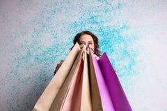 Femme de sourire heureuse aux achats montrant les sacs en papier colorés Image stock