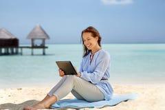Femme de sourire heureuse avec le PC de comprimé sur la plage d'été images stock