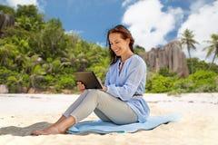 Femme de sourire heureuse avec le PC de comprimé sur la plage d'été photos libres de droits