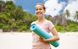 Femme de sourire heureuse avec le tapis d'exercice au-dessus de la plage photos stock