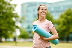 Femme de sourire heureuse avec le tapis d'exercice au parc de ville photo stock