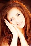 Femme de sourire heureuse avec les cheveux rouges Photo stock