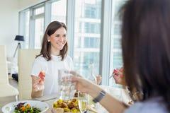 Femme de sourire heureuse dînant avec des amis Photographie stock libre de droits