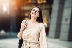Femme de sourire heureuse d'affaires en verres sortis au sujet de la nouvelle position du travail image stock