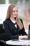 Femme de sourire heureuse d'affaires travaillant dans le bureau moderne sur l'ordinateur portable Photo stock