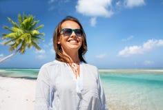 Femme de sourire heureuse dans des lunettes de soleil au-dessus de plage images libres de droits
