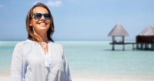 Femme de sourire heureuse dans des lunettes de soleil au-dessus de plage photos libres de droits