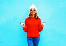 Femme de sourire heureuse dans le chandail et le chapeau tricotés sur un bleu Photos libres de droits