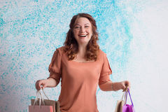 Femme de sourire heureuse dans le chemisier orange tenant des sacs en papier d'achats Photos stock