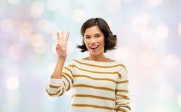 Femme de sourire heureuse montrant trois doigts photographie stock libre de droits