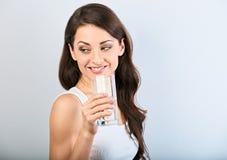 Femme de sourire heureuse positive avec la peau saine et les longs cheveux bouclés buvant l'eau pure et regardant en arrière sur  photos stock