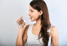 Femme de sourire heureuse positive avec la peau saine et les longs cheveux bouclés buvant l'eau pure sur le fond bleu closeup image stock