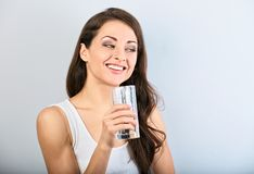 Femme de sourire heureuse positive avec la peau saine et les longs cheveux boucl?s buvant l'eau pure et recherchant closeup image libre de droits