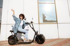 Femme de sourire heureuse s'asseyant sur une motocyclette moderne Image libre de droits