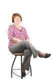 Femme de sourire heureuse s'asseyant sur une présidence de bar image stock