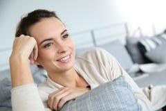 Femme de sourire heureuse sur le sofa détendant et rêvassant Photos stock