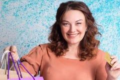 Femme de sourire heureuse tenant les sacs en papier colorés d'achats, bankin Photographie stock