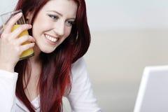 Femme de sourire heureux à la maison sur l'ordinateur portatif Image stock