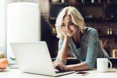 Femme de sourire de jeunes belle à l'aide de l'ordinateur portable à la maison image libre de droits