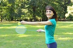 Femme de sourire jouant le badminton en parc d'été Photos stock