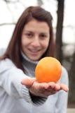 Femme de sourire jugeant orange en parc Photo libre de droits
