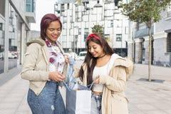 Femme de sourire lui montrant de nouveaux vêtements à son ami dans le stree Photos stock