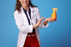 Femme de sourire de médecin appliquant le bloc du soleil sur le bleu photo libre de droits