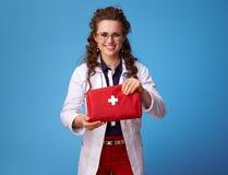 Femme de sourire de médecin montrant la trousse de premiers soins sur le bleu images stock