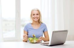 Femme de sourire mangeant de la salade avec l'ordinateur portable à la maison Photo libre de droits