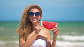Femme de sourire mangeant la pastèque sur la plage Femme mangeant du fruit savoureux d'été heure d'?t? heureuse banque de vidéos