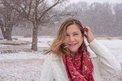 Femme de sourire marchant dans les bois tandis que les flocons de neige tombent photo libre de droits