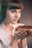 Femme de sourire mignonne de brune tenant des grains de café dans la tasse en bois Photos libres de droits