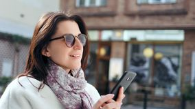 Femme de sourire de mode enthousiaste de rue causant utilisant le smartphone extérieur au plan rapproché moderne de ville banque de vidéos