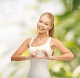 Femme de sourire montrant le geste de forme de coeur Photographie stock