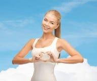 Femme de sourire montrant le geste de forme de coeur Images stock