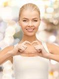Femme de sourire montrant le geste de forme de coeur Photos stock