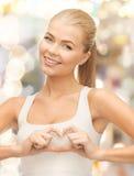 Femme de sourire montrant le geste de forme de coeur Image libre de droits