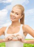 Femme de sourire montrant le geste de forme de coeur Photographie stock libre de droits