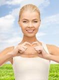 Femme de sourire montrant le geste de forme de coeur Photo libre de droits