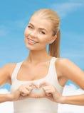 Femme de sourire montrant le geste de forme de coeur Image stock