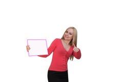 Femme de sourire montrant le panneau d'affichage vide d'affiche Photographie stock libre de droits