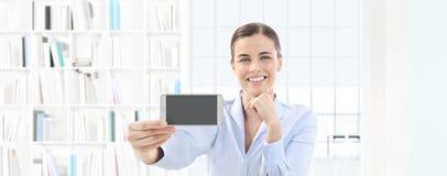 Femme de sourire montrant le smartphone dans sa main sur le bureau intérieur Photos libres de droits
