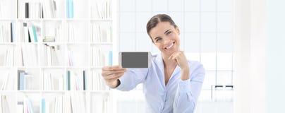 Femme de sourire montrant le smartphone dans sa main sur le bureau intérieur Images stock