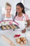 Femme de sourire montrant les biscuits fraîchement cuits au four à l'ami Photos stock