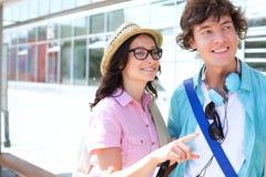 Femme de sourire montrant quelque chose équiper tout en attendant à l'arrêt d'autobus Images stock