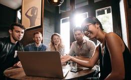 Femme de sourire montrant quelque chose sur l'ordinateur portable à ses amis Photos libres de droits