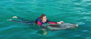 Femme de sourire nageant avec le dauphin photo stock