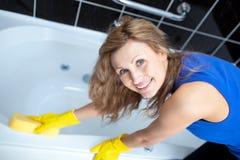 Femme de sourire nettoyant un bain Photographie stock