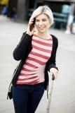 Femme de sourire parlant au téléphone intelligent en dehors de la gare Images libres de droits