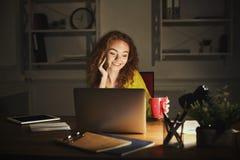 Femme de sourire parlant au téléphone tout en travaillant sur l'ordinateur portable Photo stock